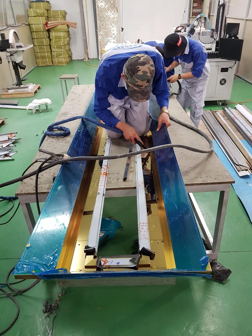 Công nhân tại Vạn Xuân đang gia công khung cửa inox mạ vàng