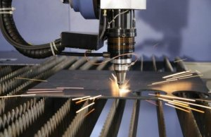 Đầu tia laser đang cắt trên tấm thép